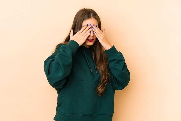 Young caucasian woman isolated en beige background afraid covering eyes with hands.