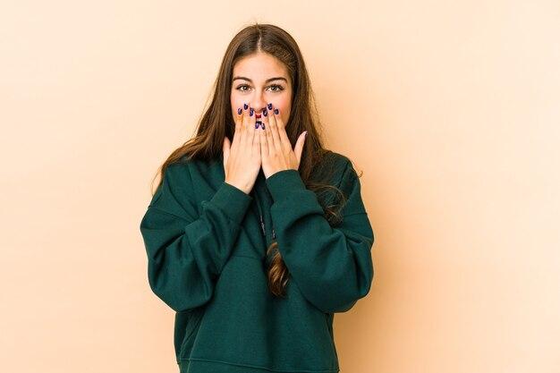 Молодая кавказская женщина изолирована на бежевом фоне в шоке, прикрывая рот руками, стремясь открыть для себя что-то новое.