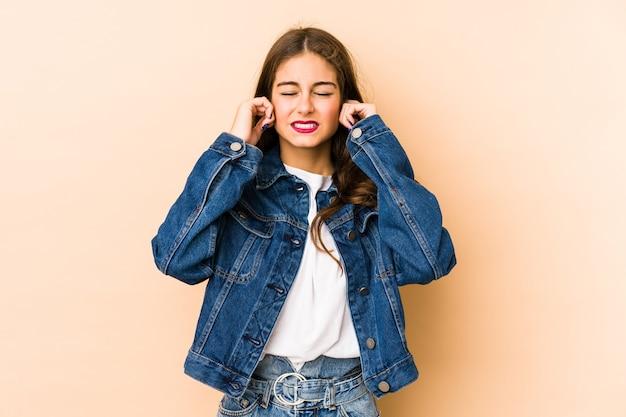 若い白人女性は、大きな環境によってストレスと必死になって、指で耳を覆っているベージュ色で孤立しました。