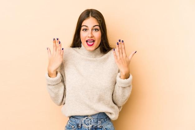 若い白人女性は手で10番を示すベージュを分離しました。