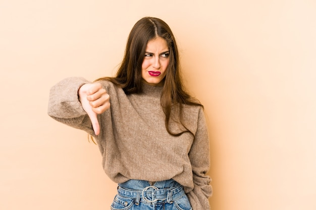 Young caucasian woman isolated en beige space showing thumb down and expressing dislike.