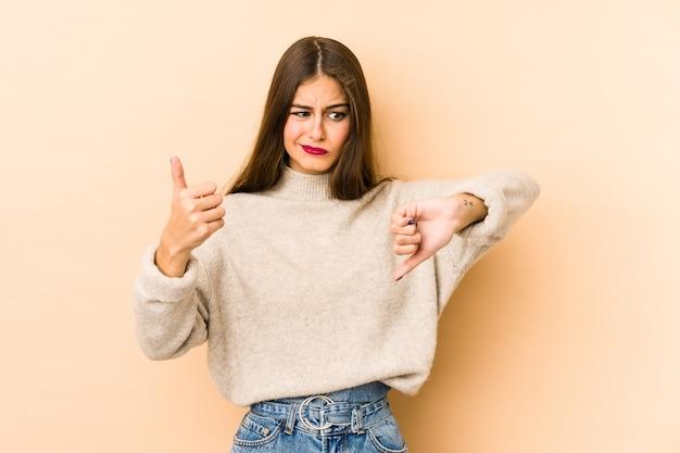 若い白人女性は、親指を上に、親指を下に、難しい選択の概念を示すベージュのスペースを分離しました