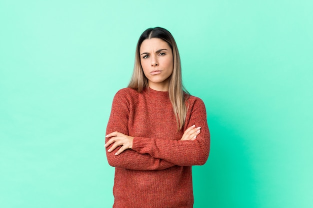 Young caucasian woman isolated frowning face in displeasure, keeps arms folded.