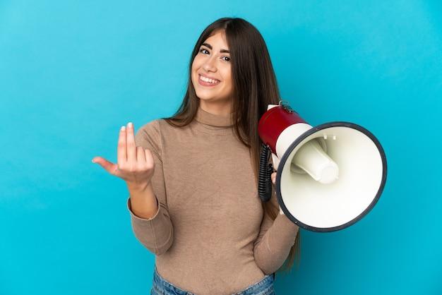 メガホンを持って、手で来るように誘う孤立した若い白人女性