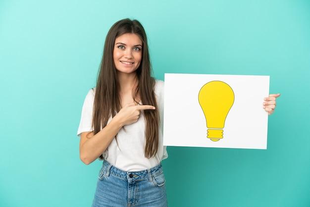 Молодая кавказская женщина изолирована, держа плакат со значком лампочки и указывая на него