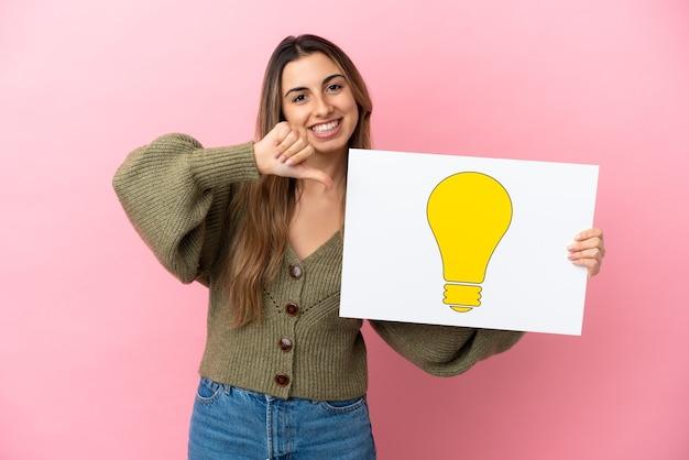 Молодая кавказская женщина изолирована, держа плакат с иконой лампочки с гордым жестом