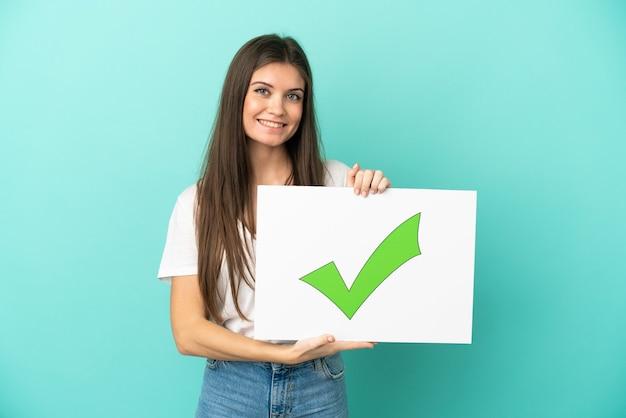 幸せな表情で緑のチェック マーク アイコン テキスト付きのプラカードを持って分離された若い白人女性