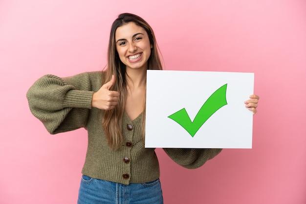 緑のチェック マーク アイコンを親指でテキスト付きのプラカードを持って分離された若い白人女性