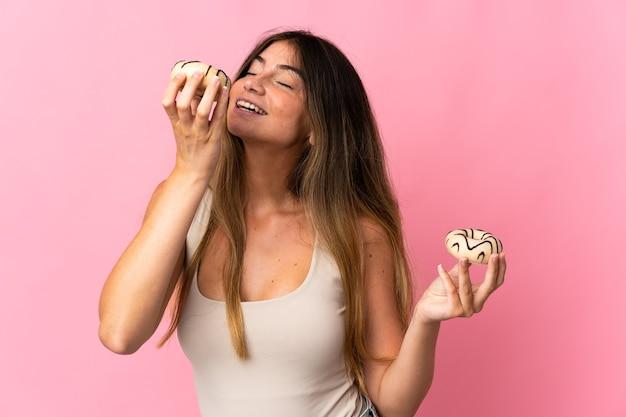 若い白人女性が幸せな表情でドーナツを保持して孤立