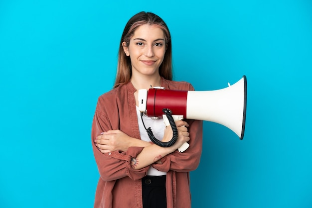 Young caucasian woman isolated holding a megaphone and smiling