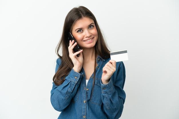 Молодая кавказская женщина изолирована, разговаривает по мобильному телефону и держит кредитную карту