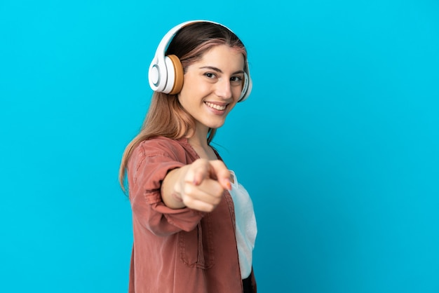 Young caucasian woman isolated listening music and pointing to the front