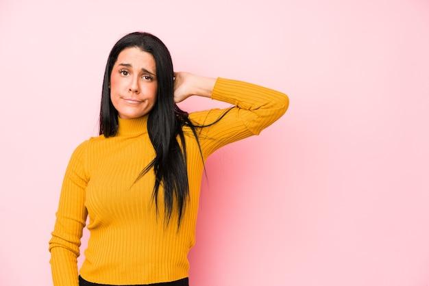 Молодая кавказская женщина изолирована на розовой стене, касаясь затылка, думая и делая выбор.