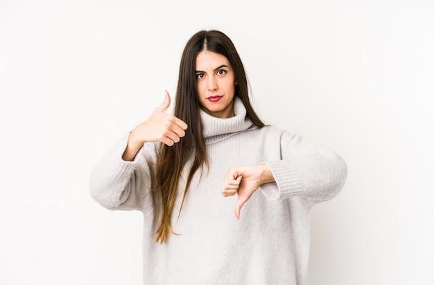 親指を上に、親指を下に示す白で隔離の若い白人女性、難しい選択の概念
