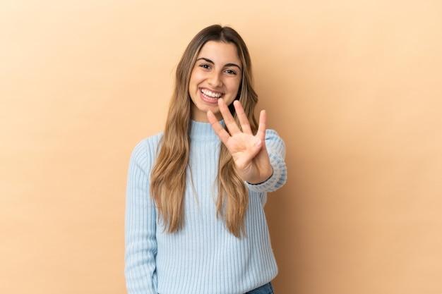 Молодая кавказская женщина изолирована на бежевом фоне счастлива и считает четыре пальцами