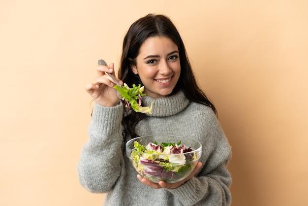 幸せな表情でサラダのボウルを保持しているベージュの背景に分離された若い白人女性