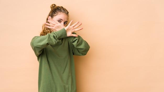 ベージュの背景で隔離された若い白人女性は、2つの腕を交差させたまま、概念を否定します。