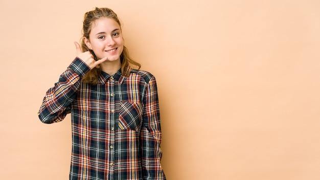 指で携帯電話のジェスチャーを示すベージュ色の背景に分離された若い白人女性。