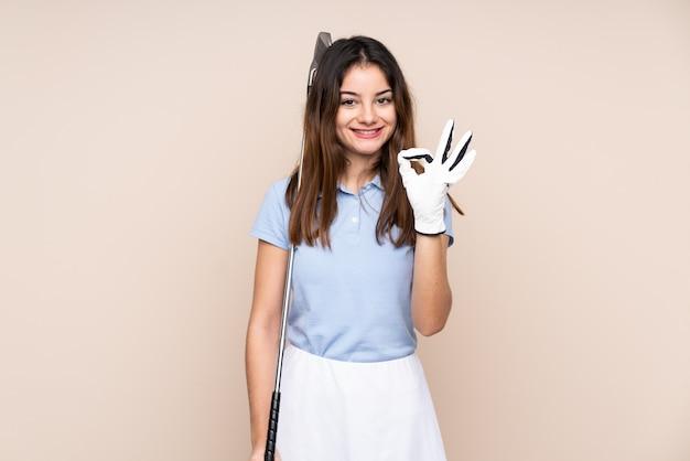 베이지 색 골프 확인 서명 만들기에 고립 된 젊은 백인 여자