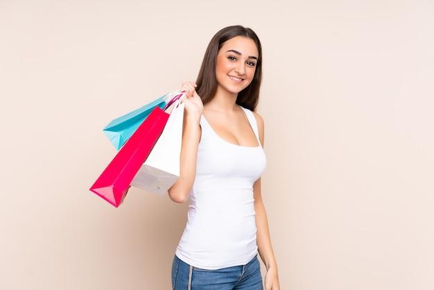 ショッピングバッグを保持し、笑顔のベージュの壁に分離された若い白人女性