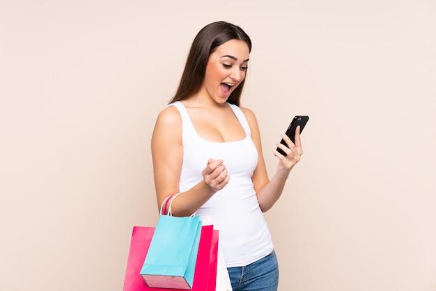 쇼핑백을 들고 친구에게 그녀의 휴대 전화로 메시지를 작성하는 베이지 색 벽에 고립 된 젊은 백인 여자