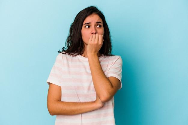 파란색 배경에 고립된 젊은 백인 여성은 손톱을 물어뜯고 긴장하고 매우 불안해합니다.