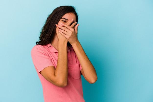 青い背景で隔離された若い白人女性は、恥ずかしい顔を覆って、指を通してカメラで点滅します。