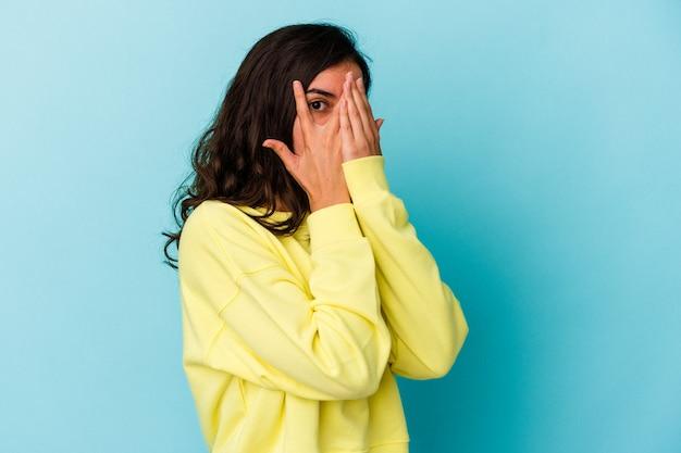 青い背景に隔離された若い白人女性は、おびえ、神経質な指を点滅します。