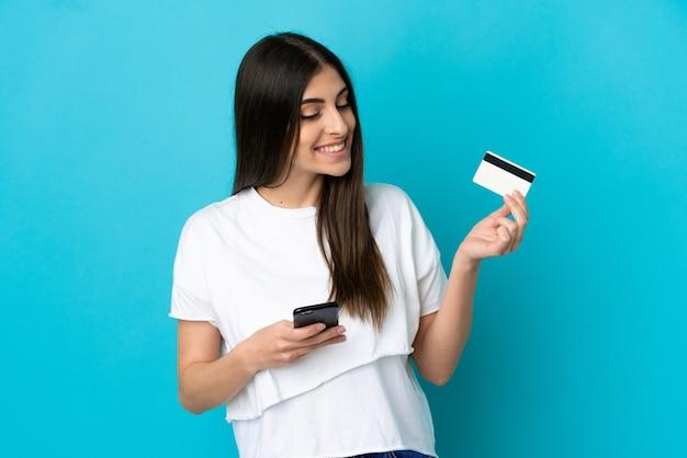 생각하는 동안 신용 카드로 모바일로 구매하는 파란색 배경에 고립 된 젊은 백인 여자