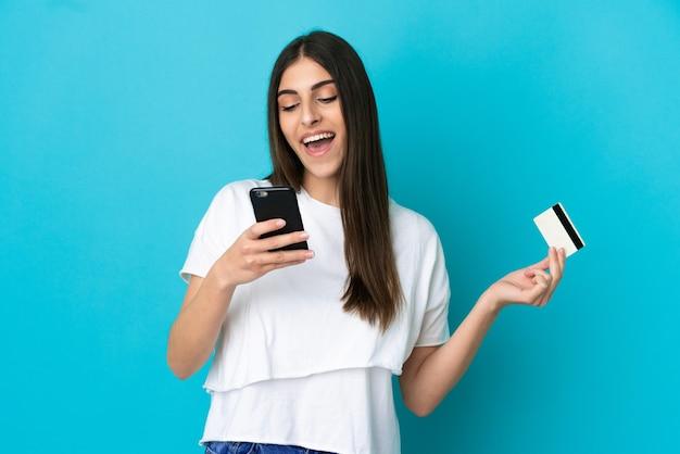 신용 카드로 모바일로 구매 파란색 배경에 고립 된 젊은 백인 여자
