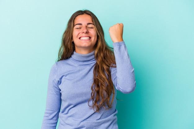 勝利、情熱と熱意、幸せな表現を祝う青い背景で隔離の若い白人女性。