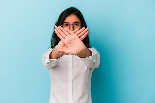 Молодая кавказская женщина изолирована на синем фоне, делая жест отрицания