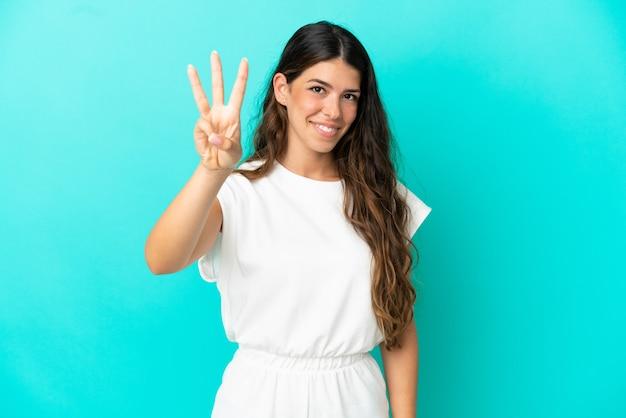 幸せな青い背景で隔離の若い白人女性と指で3を数える