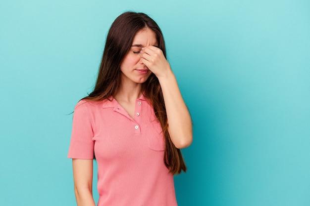 顔の正面に触れて、頭痛を持っている青い背景で隔離の若い白人女性。