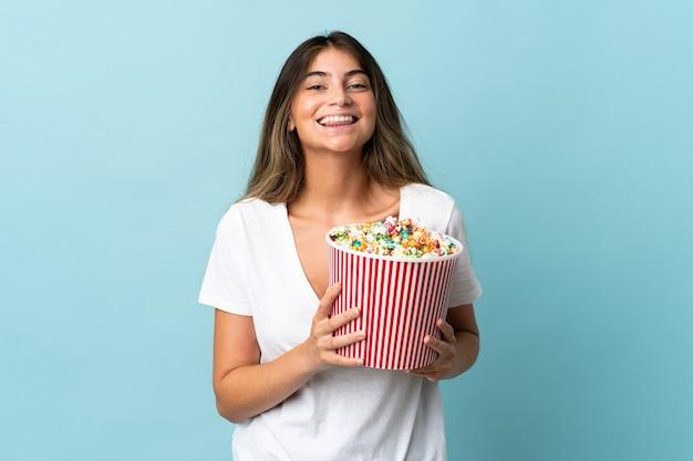 Молодая кавказская женщина изолирована на синем фоне, держа большое ведро попкорна
