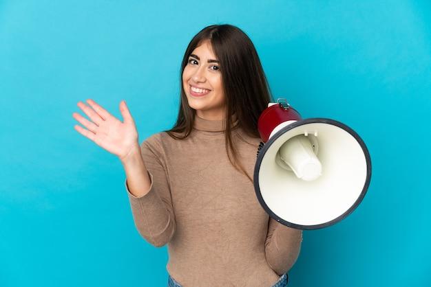 Молодая кавказская женщина изолирована на синем фоне, держа мегафон и салютуя рукой с счастливым выражением лица