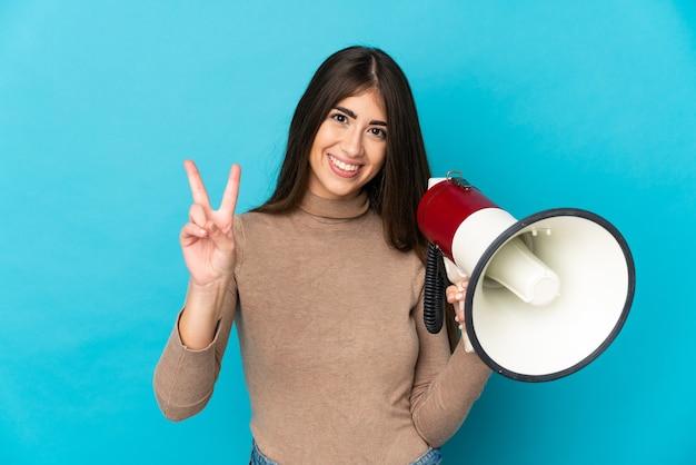 Молодая кавказская женщина, изолированная на синем фоне, держит мегафон и улыбается и показывает знак победы