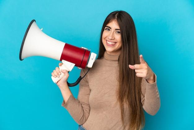 Молодая кавказская женщина изолирована на синем фоне, держа мегафон и улыбаясь, указывая вперед