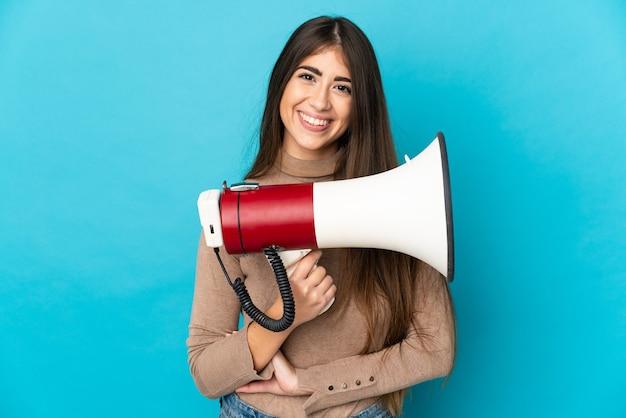 Молодая кавказская женщина изолирована на синем фоне с мегафоном и улыбается
