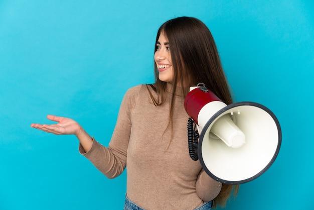 Молодая кавказская женщина изолирована на синем фоне с мегафоном и с удивленным выражением лица