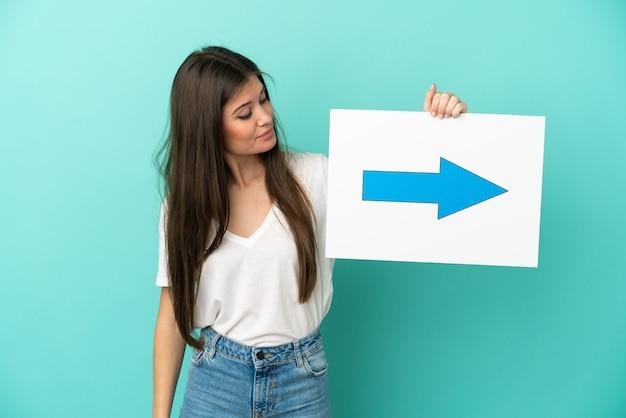 矢印記号の付いたプラカードを持って青の背景に分離された若い白人女性