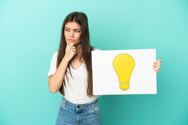 Молодая кавказская женщина изолирована на синем фоне, держа плакат со значком лампочки и думая