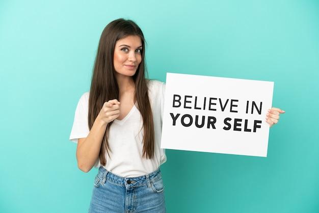 Молодая кавказская женщина, изолированная на синем фоне, держит плакат с текстом «верь в себя» и указывает вперед