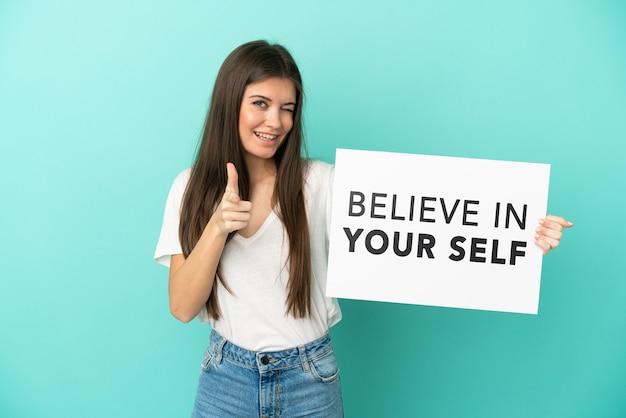 青の背景に若い白人女性が、自分を信じて正面を向いたプラカードを持って