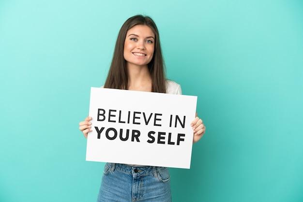 텍스트와 현수막을 들고 파란색 배경에 고립 된 젊은 백인 여자는 행복 한 표정으로 자신을 믿으십시오