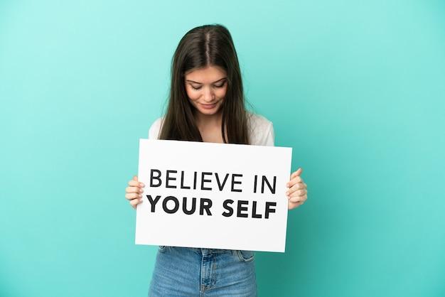 파란색 배경에 격리된 백인 젊은 여성이 자신을 믿으라는 문구가 적힌 플래카드를 들고 있습니다.