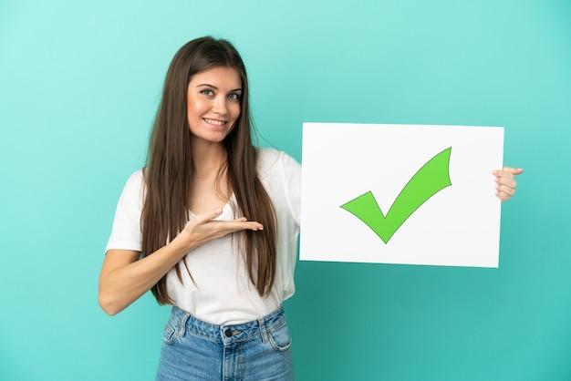 텍스트 녹색 확인 표시 아이콘으로 현수막을 들고 그것을 가리키는 파란색 배경에 고립 된 젊은 백인 여자