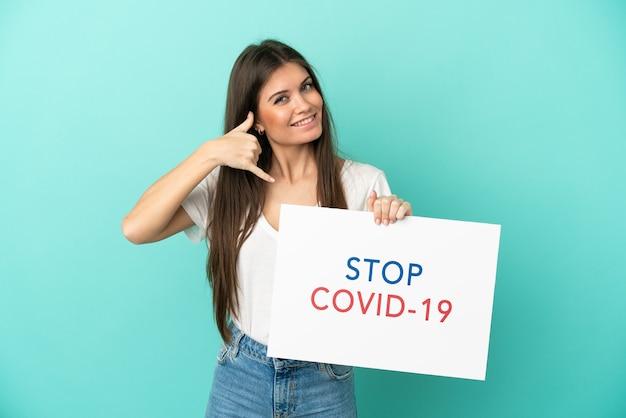 青の背景に分離された若い白人女性がテキストstopcovid 19のプラカードを保持し、電話ジェスチャーを行う