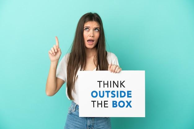 텍스트와 현수막을 들고 파란색 배경에 고립 된 젊은 백인 여자는 상자 밖에서 생각하고 생각