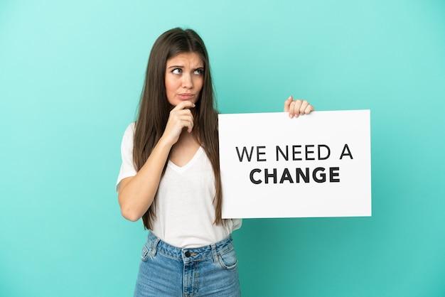 テキストとプラカードを保持している青い背景で隔離の若い白人女性私たちは変化と思考が必要です